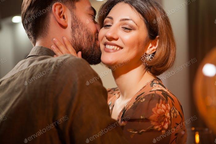 Hübscher junger Mann sanft küssen seine Freundin Wange in ein vintage pub