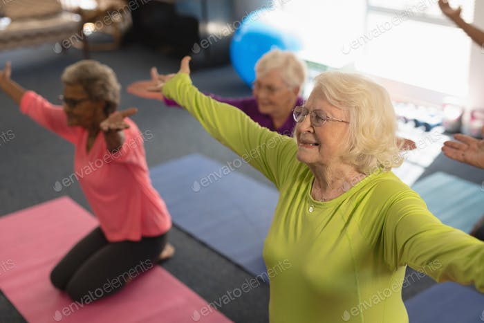 Happy senior people exercising in yoga position in fitness studio