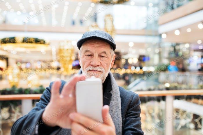 Senior man with smartphone doing Christmas shopping.