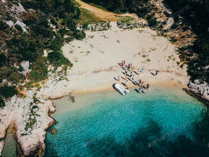 People on a wild beach near a motorboat