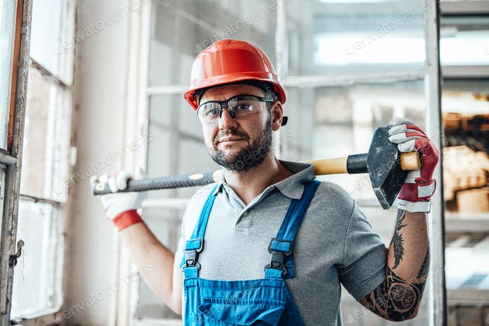 Muscular construction worker stands by the window and holds a big sledgehammer