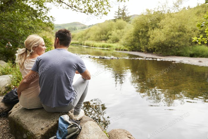 Couple On Hike Looking Out Over River In UK Lake District