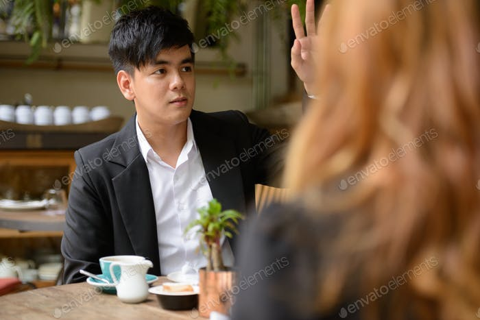 Young Asian business couple together at the coffee shop