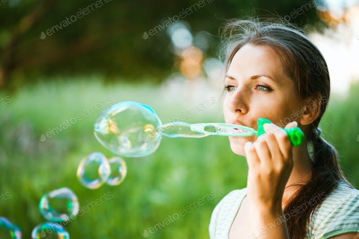 Mädchen bläst Seifenblasen in die park