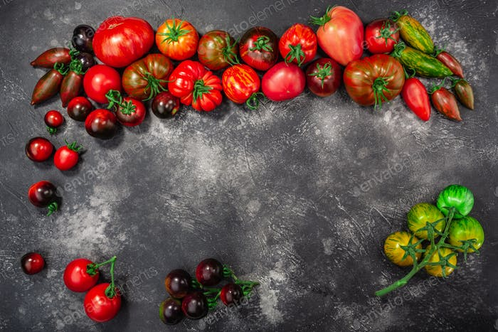 Heirloom tomatoes on dark grey concrete backdrop,  top view