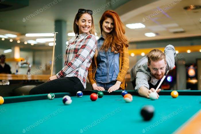 Happy friends enjoying playing pool