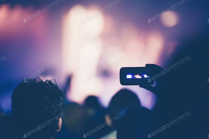 Fan taking photo of concert at festival with a mobile phone