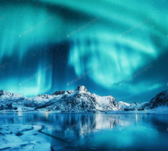 Aurora borealis above snowy mountains, frozen sea coast