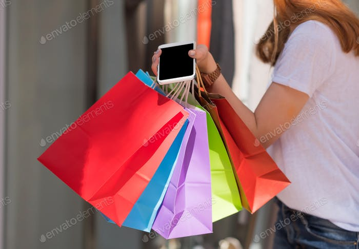 Women holds a smartphone and a shopping bag together,Shopping women concept.