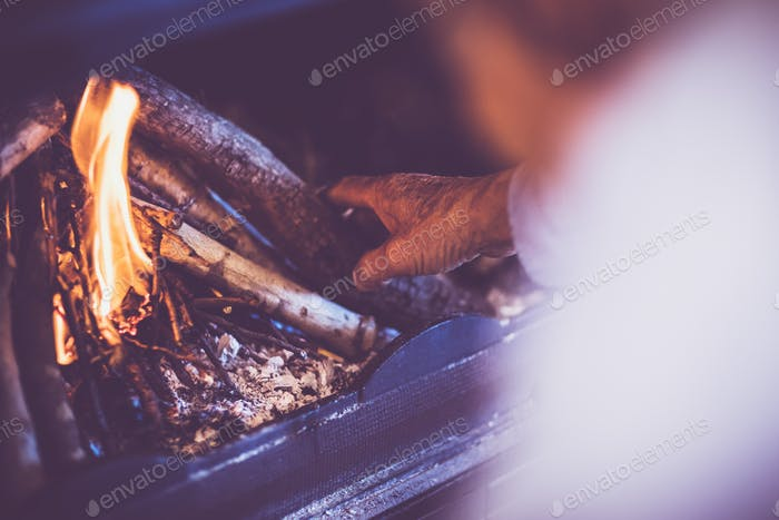 Mann entzündet ein Feuer im Kamin