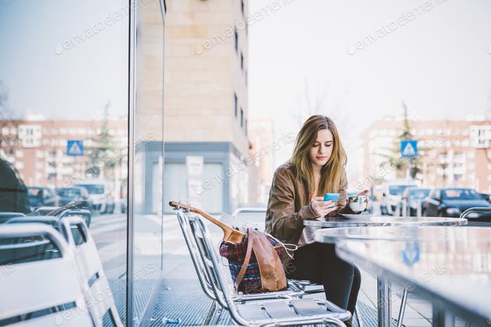 Young beautiful caucasian woman sitting on a bar having a cup of