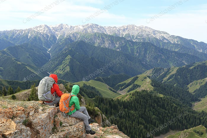 Two successful hikers enjoy the view on mountain top