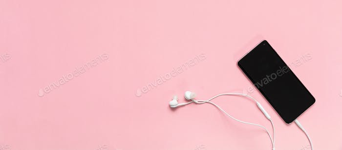 Smartphone and earphones against pink background