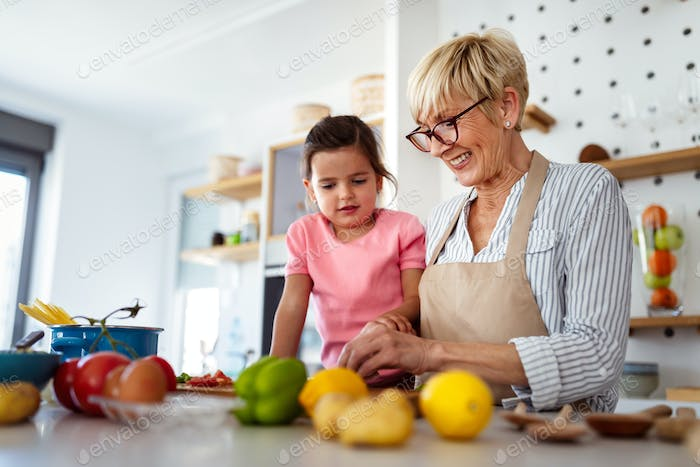 Grandmother and granddaughter are cooking on kitchen. Family fun love generation concept