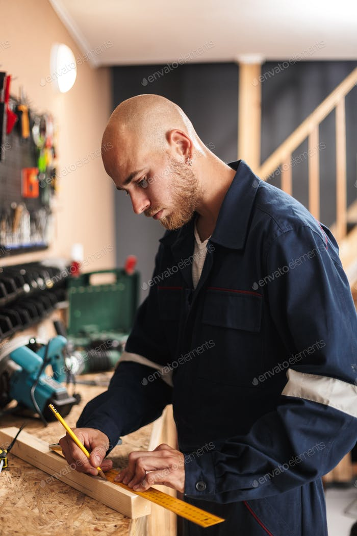 Foreman in work clothes dreamily using measuring tape in worksho