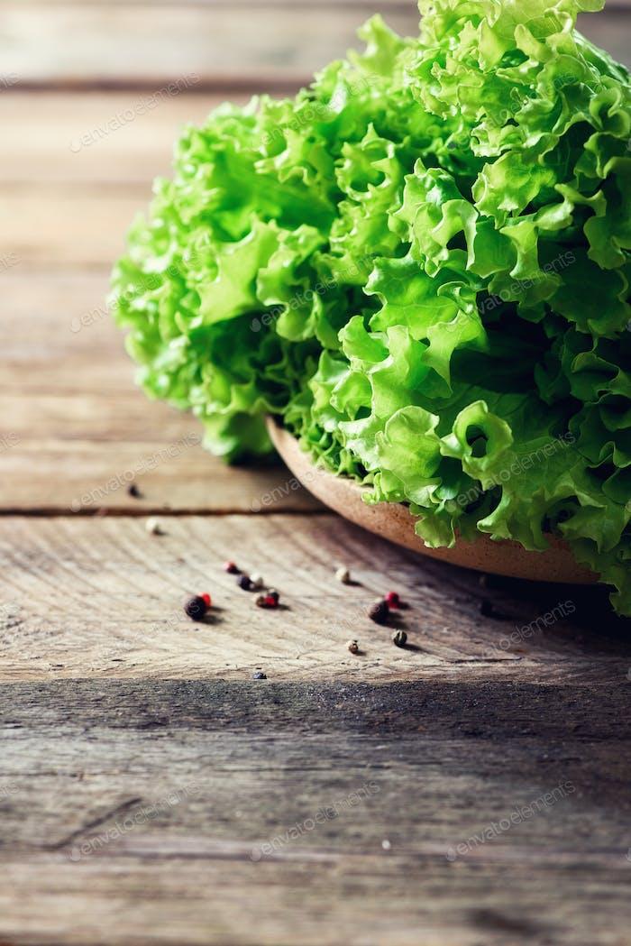 Frischer Bio-Salatsalat auf hölzernem Hintergrund mit Pfeffer. Gesundes Essen, roh und vegetarisch