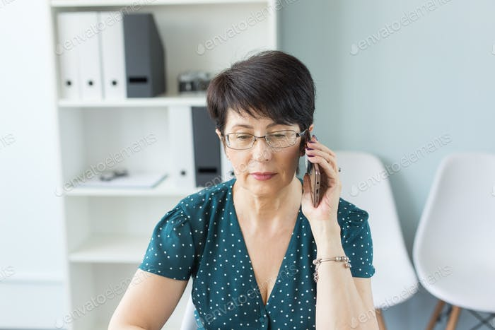 People, technology and communication concept - Middle aged business woman at office making a phone
