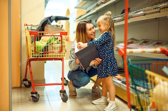 Mother and little girl with carts in kid's store