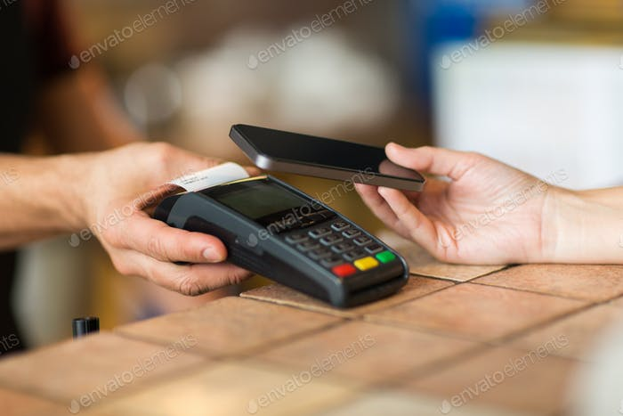 hands with payment terminal and smartphone at bar