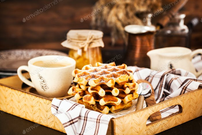 Breakfast with belgian waffles, jam and coffee on tray, rustic b