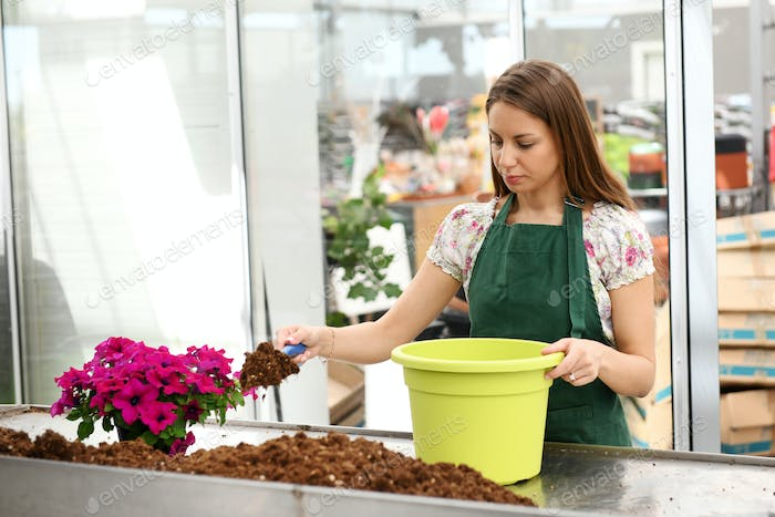 Young lady shoveling dirt into flower pot