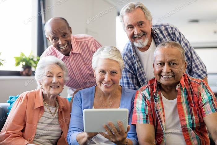 Smiling senior people with digital tablet