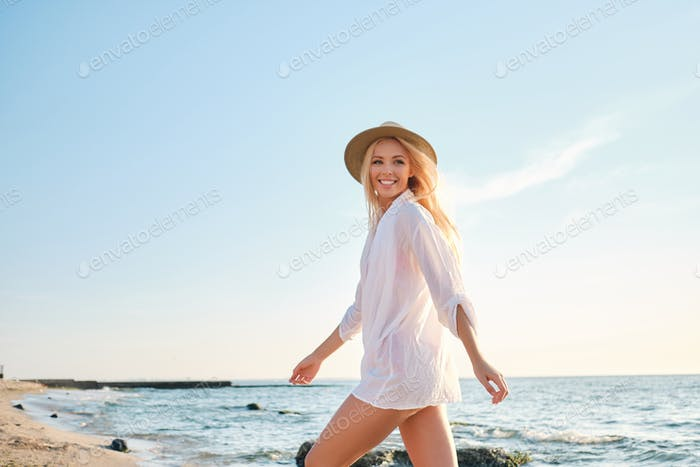 Young gorgeous smiling blond woman in white shirt and hat happily walking by the sea