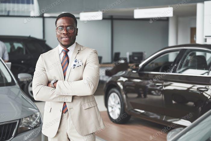 Young black businessman on auto salon background. Car sale and rent concept