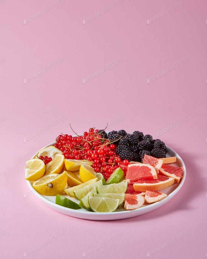 Set of different citrus fruits and berries in a plate presented on a pink background with copy space