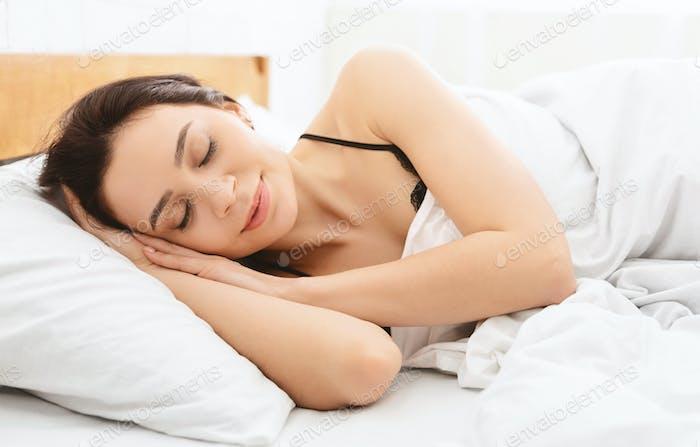 Portrait of millennial woman sleeping in bed