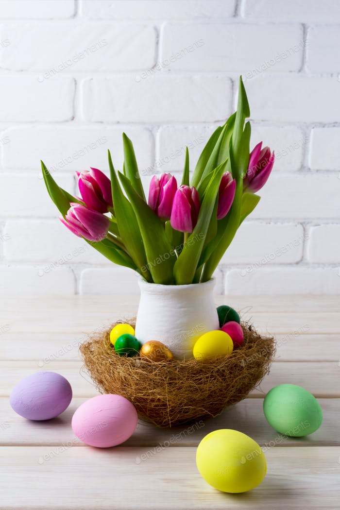 Easter table centerpiece with  nest and pink tulips in flower po