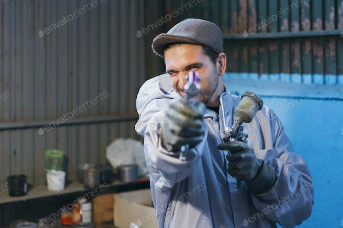 Bearded craftsman holding paint gun