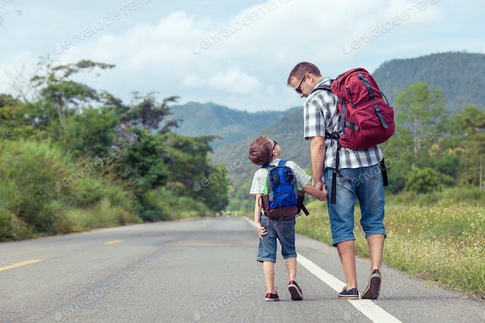 Father and son walking on the road.
