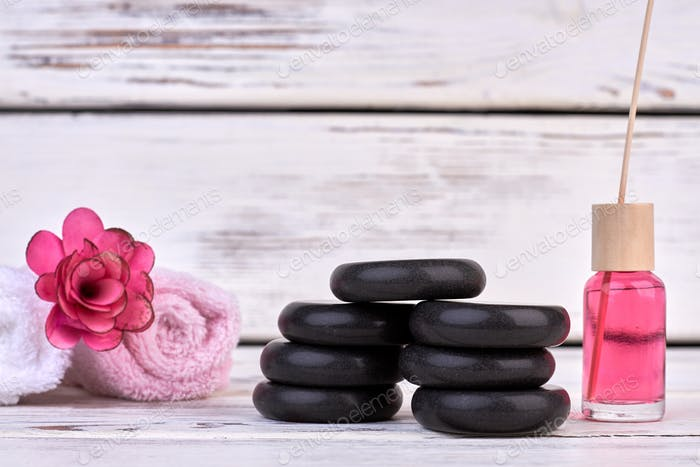 Still life black stones with rolled towels and body oil.