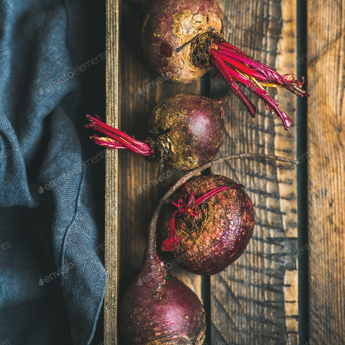 Raw organic purple beetroots in wooden box, square crop