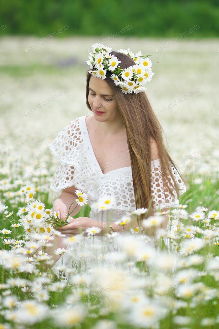 Cute girl in camomile meadow.