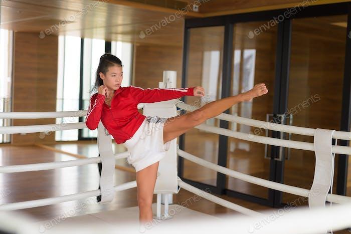 Mujer asiática kick boxer listo patear en anillo de boxeo