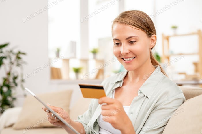 Young woman with tablet reading data on card while paying for online order