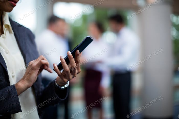 Mid section of female business executive using mobile phone