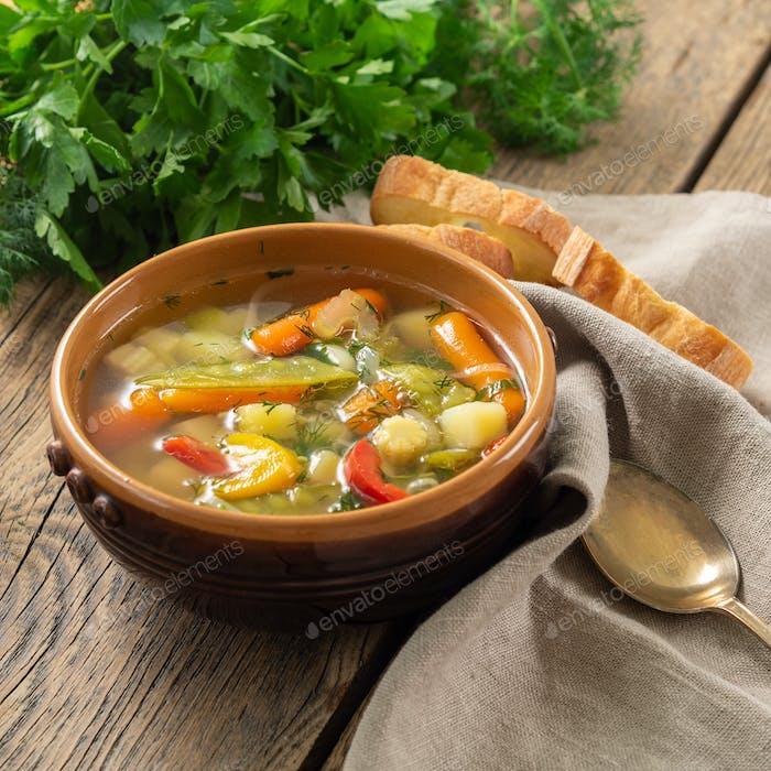 Bright spring vegetable dietary vegetarian soup. Side view, brown rustic wood background