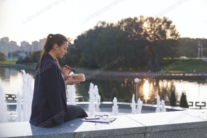 Brunette business woman eating vegetarian takeaway salad outdoor