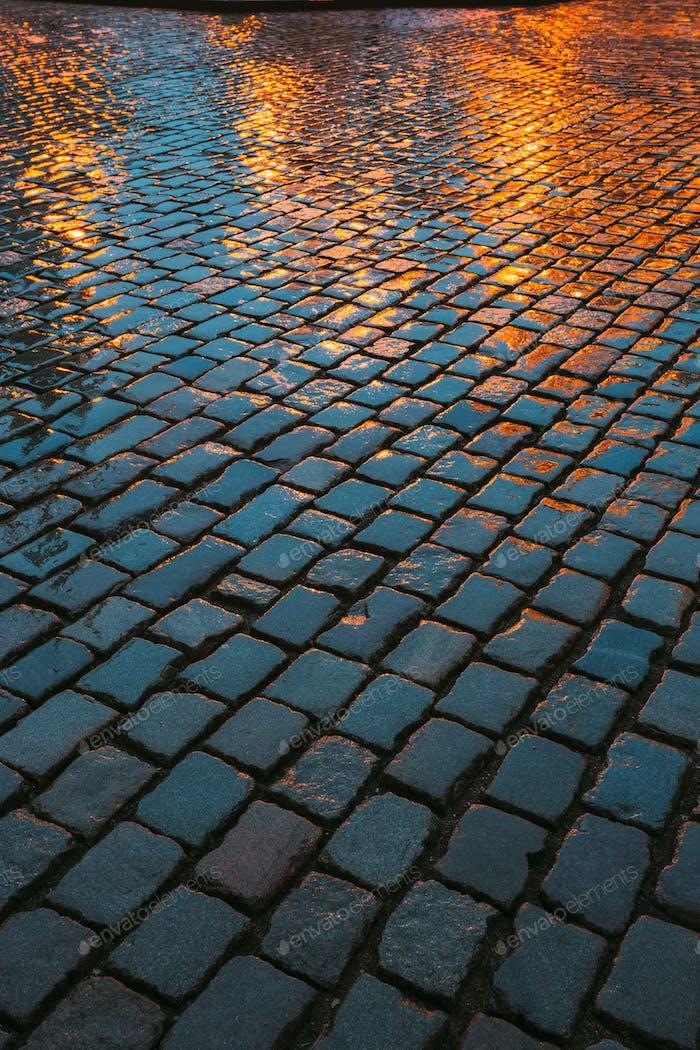 Old Streets Cobblestone abstrakter Hintergrund. Nasse Steine in Eveni