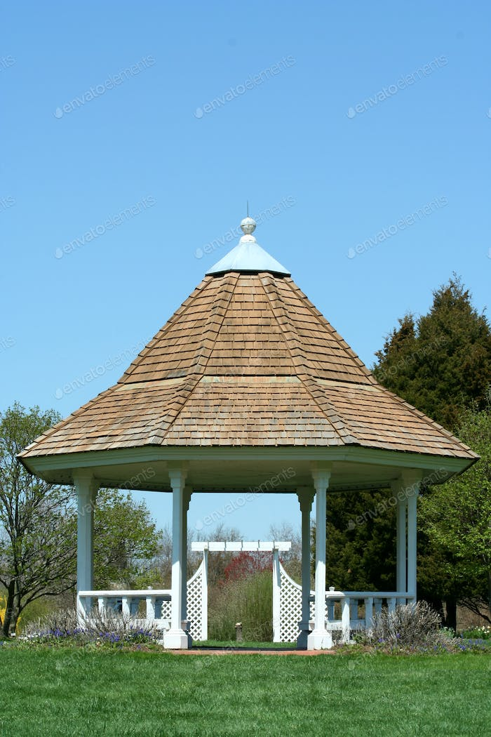 White gazebo in a park with blue sky