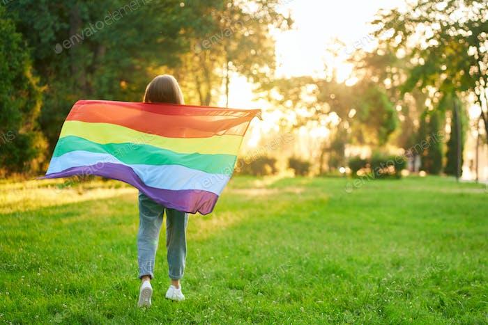 Mujer sosteniendo bandera lgbt arco iris detrás de la espalda