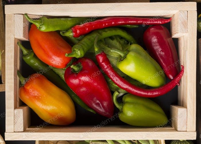 Close up of farm peppers in big wooden box