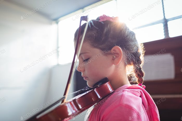 Side view of girl student rehearsing violin