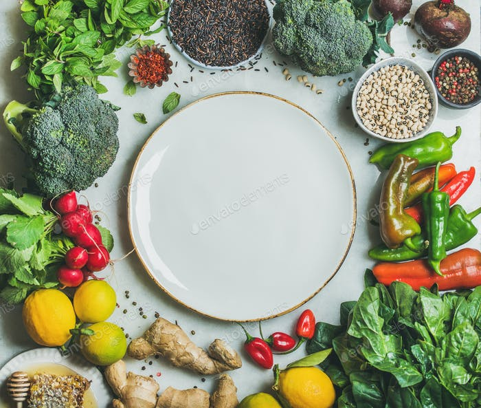 Clean eating healthy cooking ingredients and round plate in center