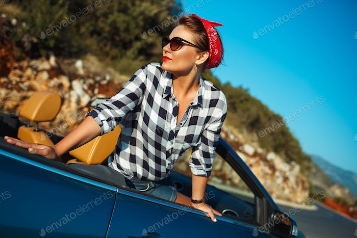 Beautiful pin up woman sitting in cabriolet, enjoying trip on lu