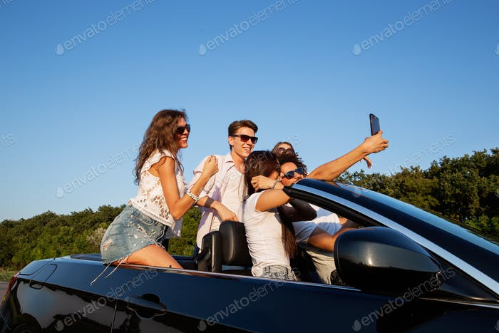 Joyful young girls and guys are sitting in a black cabriolet on the road and making selfie on a