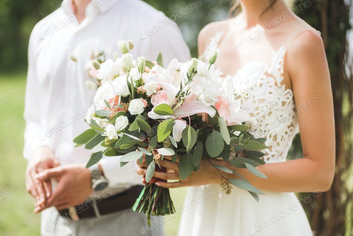 Gentle wedding bouquet with lily, pink roses and greens in loving couple hands